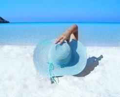 ビーチに横になる帽子の女性